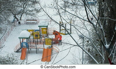 Mom and kid having fun on playground in winter -...