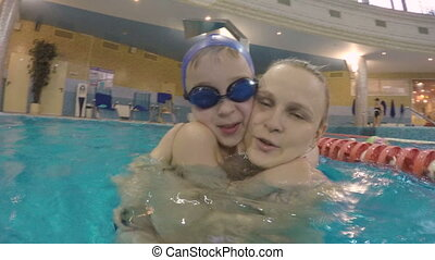 Boy in hugs of dear mother when they bathing in the pool -...