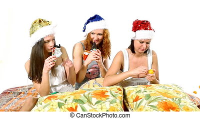 Young girls in santa hat eat chocolate on pillows -...