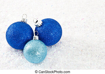 Three Blue Glittery Ornaments on Snowy Background -...