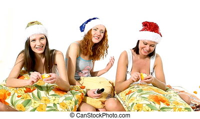 girls in santa hat eat mandarine - Young girls in santa hat...