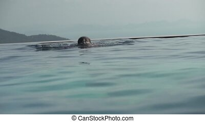 Young girl swims in outdoor pool stock footage video - Young...
