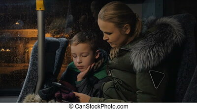 Kid with mother using cellphone in the bus - Mother and...