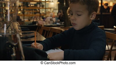Child drawing when sitting in cafe - Boy sitting at the...
