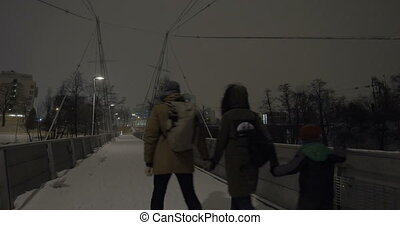Parents with child holding hands and walking in evening winter city