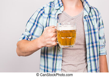 Close up of man holding a mug of beer. Background with copy...