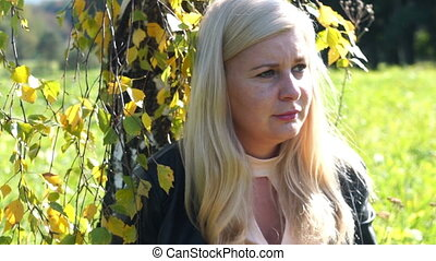 pensive frustrated beautiful Blonde woman in park sitting...