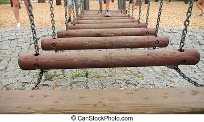 Close up of children's legs going on a suspension bridge in...