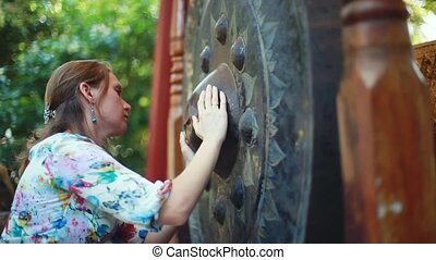 Female hands stroking the religious gong in Buddhist temple...