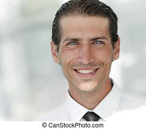 face of young businessman on background of office - closeup...