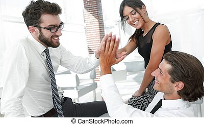members of the business team give each other high five. The...