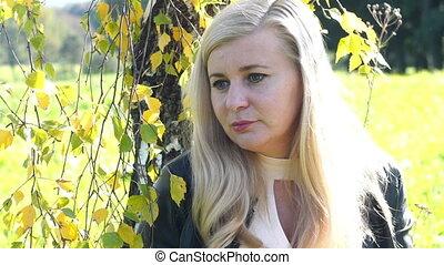 pensive beautiful Blonde woman in park - Smiling Blonde girl...