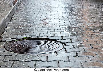 round steel sewer manhole on wet cobblestone road - round...