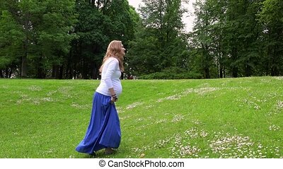 Pregnant female walking through park meadow in sunny summer...