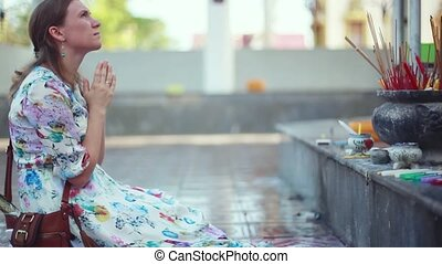 Young woman coming in temple prays on the knees multi-armed...