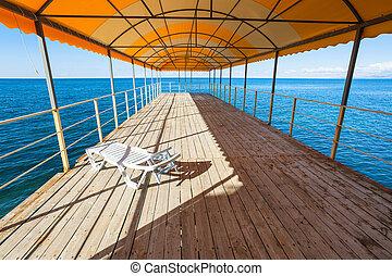one plastic sunbed in outdoor solarium over sea - travel to...