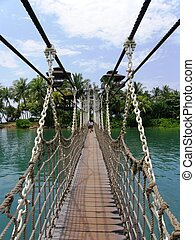 Swing bridge leading to an tropical island