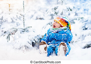 Baby playing with snow in winter. Child in snowy park. -...