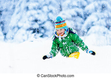 Child playing with snow in winter. Kids outdoors. - Child...