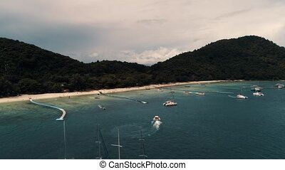 Thailand Coral Island Drone Shot Small sports boats, large catamarans, fishing schooners, active traffic near the island for the entertainment of tourists.
