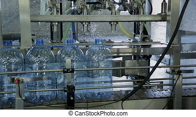 Empty plastic bottles are filled with clean water automatically.