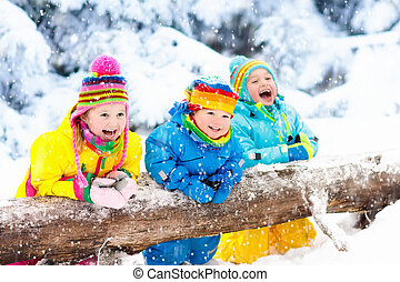 Kids playing in snow. Children play outdoors in winter...