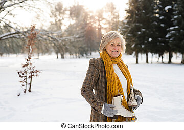Senior woman in winter nature going ice skating.