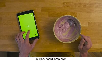 A tablet with green screen on the kitchen table - Top view....