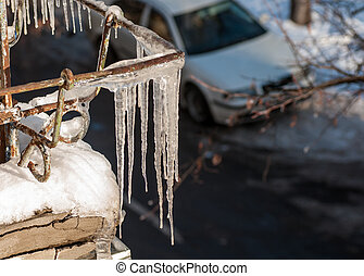 icicles hang from the roof of the balcony in the street in...