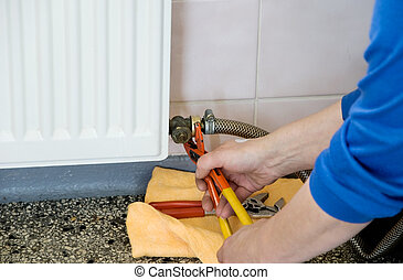 hands of a plumber repairman - hands of a plumber repairing...