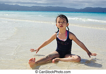 Asian kid playing on the beach - A Chinese little girl...