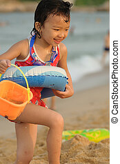 Kid playing on the beach - A Chinese little kid playing on...