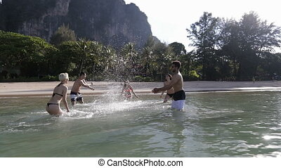 People Splashing In Water, Cheerful Young Man And Woman...