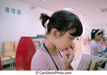 Asian kid reading book - A little Asian kid reading book in...