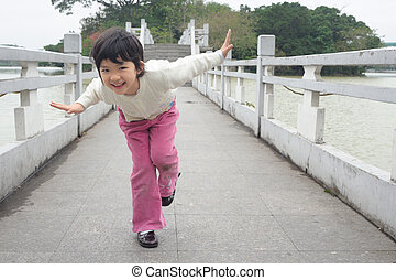 Kid playing on the bridge - An Asian little kid playing on...