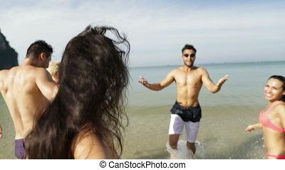 Girl Taking Selfie Of Cheerful People Running In Water On...
