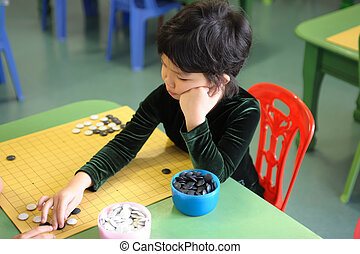 Little kid playing go game - A little chinese kid learning...