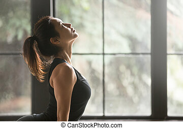Young attractive woman in upward facing dog pose, window...