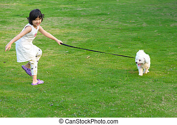 Asian kid playing with dog on the lawn