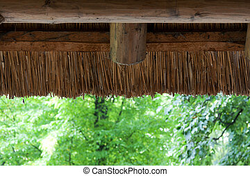 Reedy roof with wooden log on background green wood