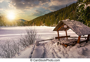 wooden bower in snowy winter forest at sunset - wooden bower...