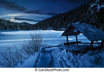 wooden bower in snowy winter forest at night - wooden bower...