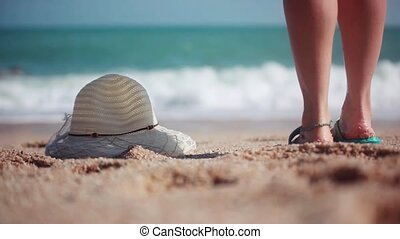 Woman coming on the Beach. She puts sunglasses next to the...
