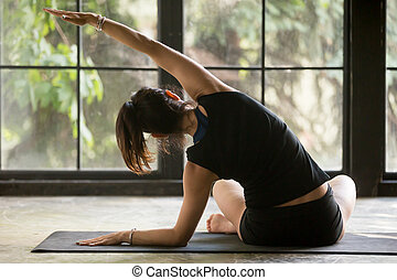 Young sporty woman in Sukhasana Side bending pose, window...