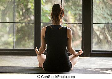 Young yogi woman in Sukhasana pose, window background -...