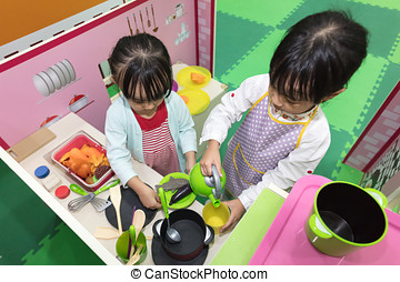 Asian Chinese little girls role-playing at kitchen at indoor...