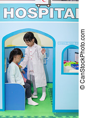 Asian Chinese little girls role-playing at hospital at...
