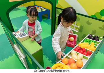 Asian Chinese little girls role-playing at fruits store at...