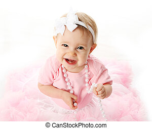 Smiling baby girl wearing pettiskirt tutu and pearls -...
