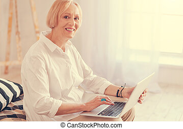 Cheerful aged woman using her laptop - New user. Waist up of...